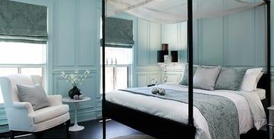 hellblaues schlafzimmer mit schwarzem bett und weißem baldachin-weißer sessel und kleiner Rundtisch-blaue fensterrollos