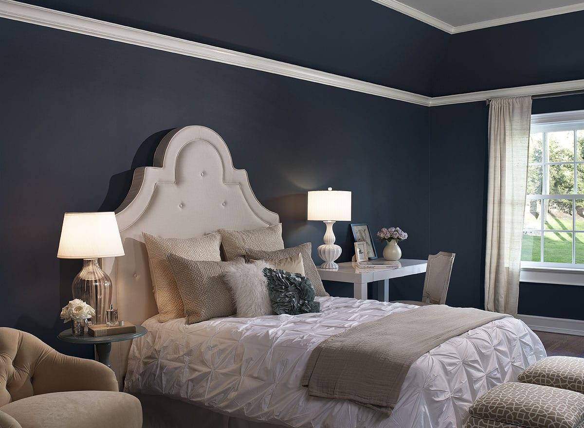 weißes bett mit kopfteil und dunkelblaue wände