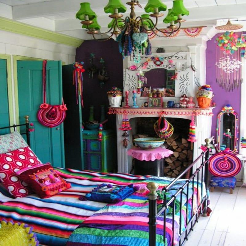 schlafzimmer mit blauer Tür und Wände in Violett-weißer Kamin-schwarzes Metallbettgestell und farbige Bettwäsche-kreative Dekenleuchte in grün