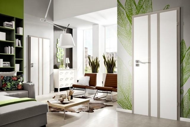 wohnzimmer grau mit mustertapete grün und kuhpelzteppich-ledersessel braun und ecksofa grau