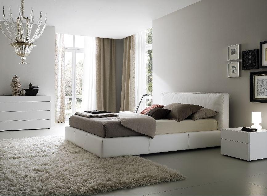 luxus schlafzimmer mit gardinen und bettwäsche in grau.fliesenboden mit weißem teppich