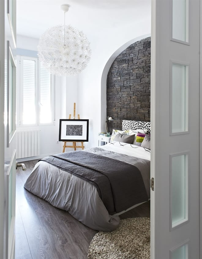 modernes kleines schlafzimmer mit bettwäsche grau und bogenwand mit natursteinverkleidung