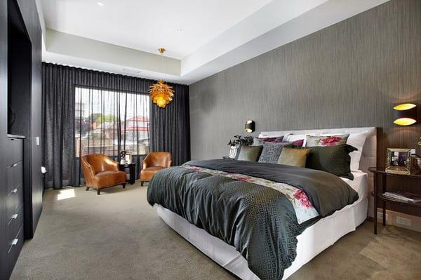 luxus schlafzimmer mit weißem bett und grauer bettwäsche-gardinen grau-ledersessel braun
