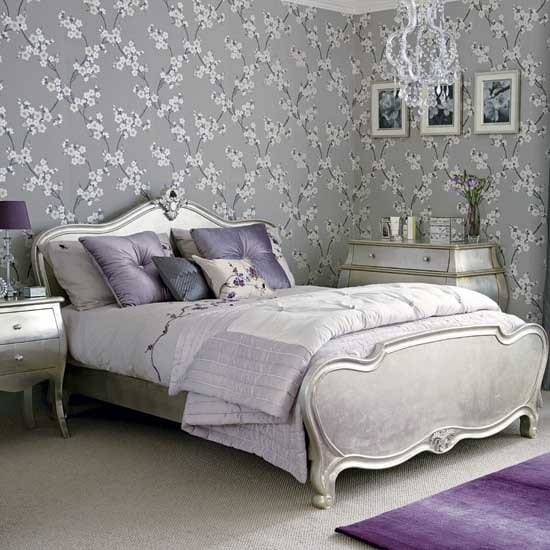 romantisches schlafzimmer mit französisches bett in silberfarbe mit lila kissen-graue tapete mit blumen-tepich lila