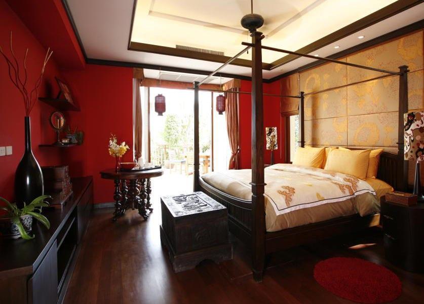 modernes schlafzimmer mit roten wänden und dunklem holzboden