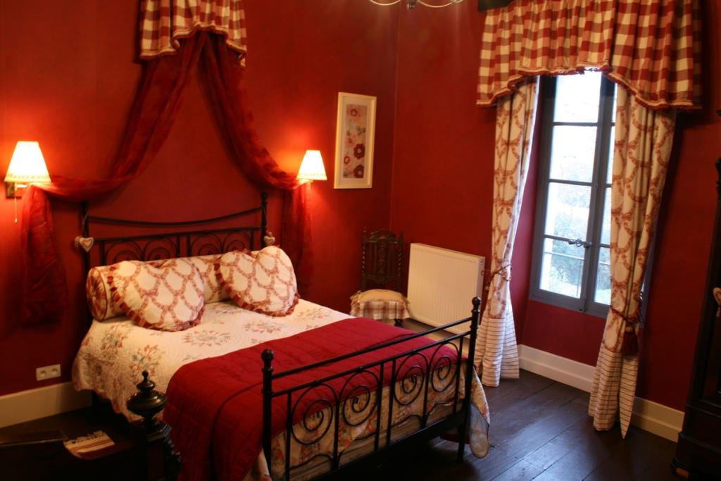 schwarzes metallbett mit roter bettdecke und herförmigen kissen