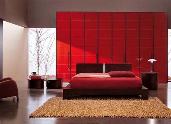 minimalistisches schlafzimmer mit holzbett und runden holztischen-bettwäsche rot