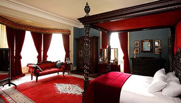 schlafzimmer einrichten mit Holzbettgestell und rotem teppich- Vorhang rot-sofa rot