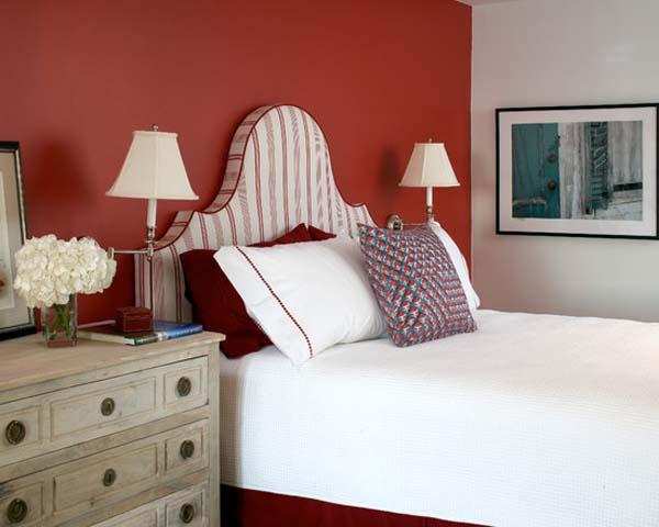 srotes bett mit weißer bettwäsche und holzkommode-rote wand im schlafzimmer