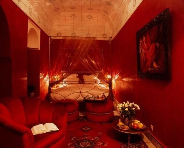 schlafzimmer mit bogendecke in weiß mit roten wänden und roten möbeln