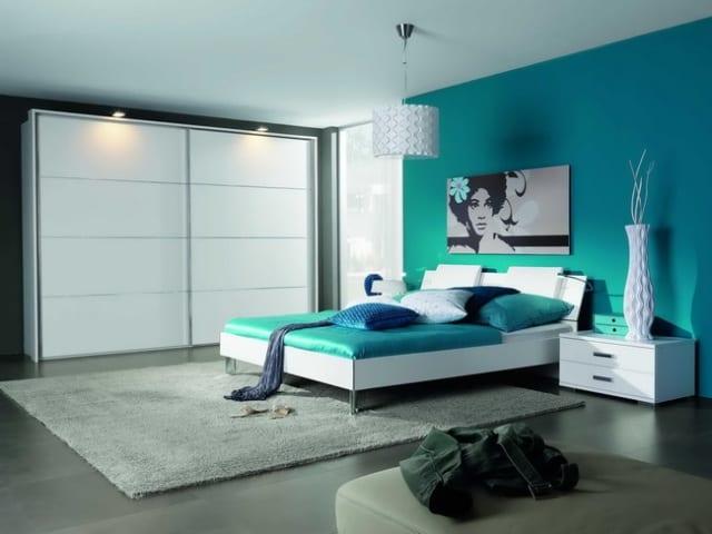 modernes Schlafzimmer mit wandfarbe blau- weißes bett mit blauer bettwäsche und blauen kissen