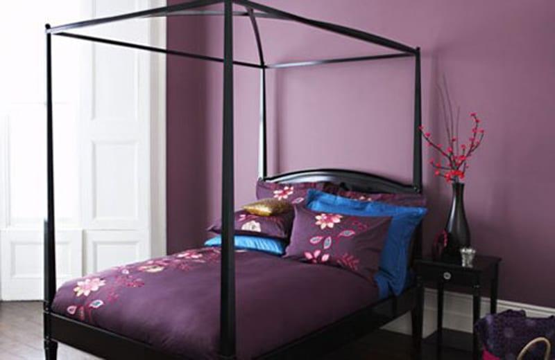 schlafzimmer gestalten - schwarzes bett mit lila bettwäsche