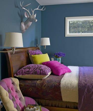 schlafzimmer blau- schlafzimmer dekorieren mit holzbett antiv und lila bettwäsche- wandgestaltung mit silbernem Hirschkopf
