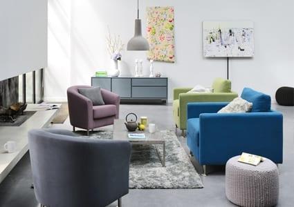 luxus wohnzimmer mit offenem Kamin und farbigen Polstersessel von fly