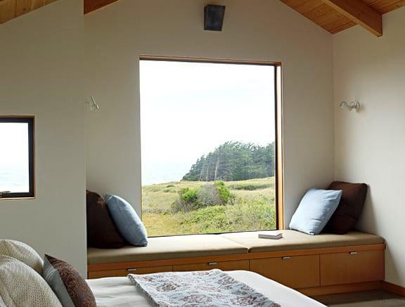 modernes schlafzimmer mit panoramafenster und sitzbank aus holz mit kissen dekorieren