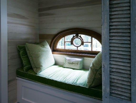 kleiner bogenfenster aus holz mit weißer fensterbank mit grüner polsterkissen