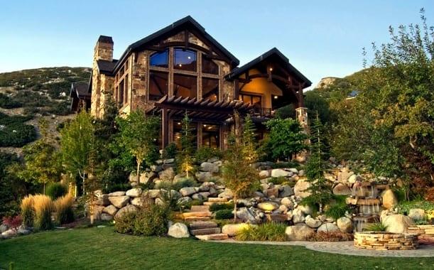 modernes haus mit steinmauerwerk und terrassiertem traumgarten