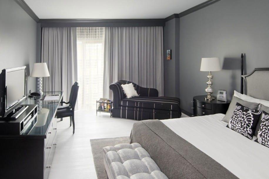 modernes schlafzimmer mit wandfabe grau schwarzen akzenten-liegesofa schwarz-bettdecke und gardinen grau