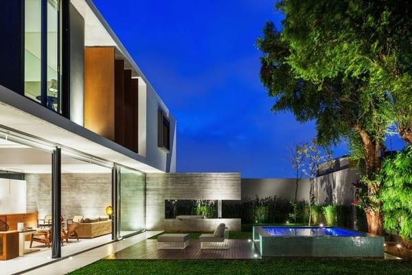 minimalistisches haus mit schiebefenstertüren und sonnenschutz aus holzdrehpanellen
