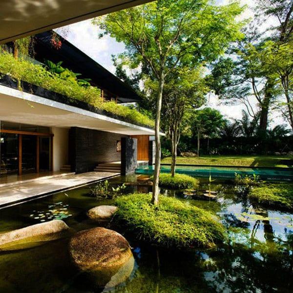 minimalistisches haus mit überdachter Gangterrasse und teichbecken