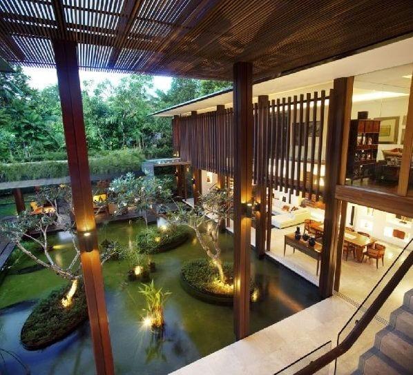 open space haus mit holzstützen und teichbeken-modernes wohnraum mit offenem überdachtem gang zum zweiten geschoß