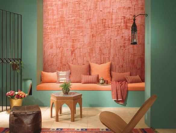 farbgestaltung wohnzimmer mit blauen wänden und Sitzfläche mit Kissen in apricot farbe