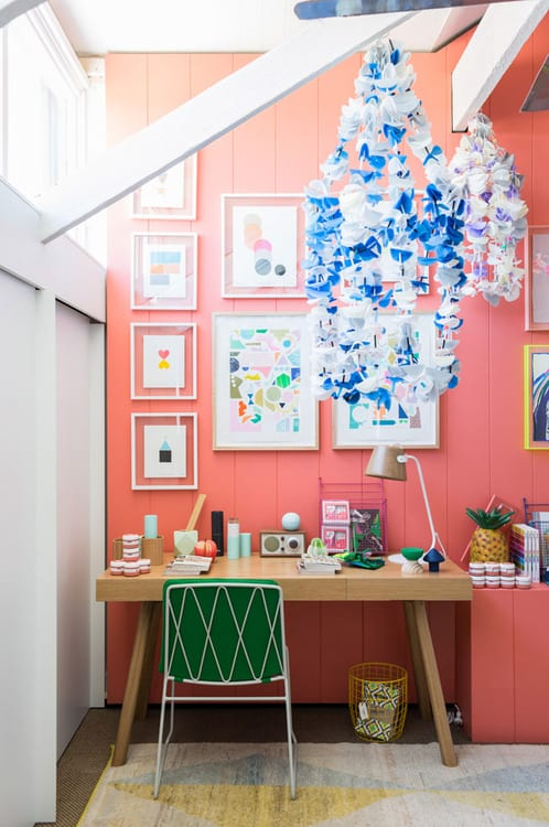 Kinderzimmer mit Holzwand in pink und sichtbare weiße Dachkonstruktion- schreibtisch aus holz-weißer metallstuhl mit grünen kissen