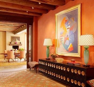 wohnzimmer mit oranger Wand und sichtbaren Holzdeckenbalken-moderne kommode schwarz-blaue tischleuchten
