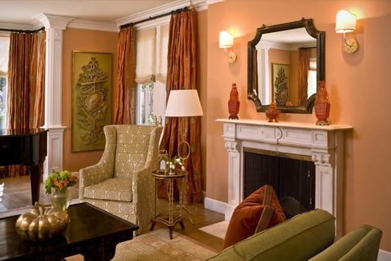 wohnzimmer mit weißem Kamin und sessel in Olivengrün- gardinen in rostfarbe