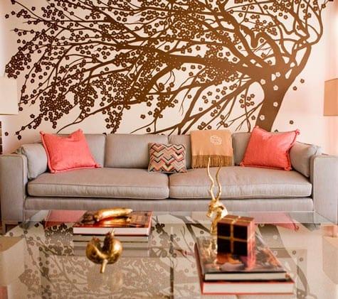 wohnzimmer mit sofa grau und rosafarbigen kissen-braunes wandtattoo baum-wand hellrosa