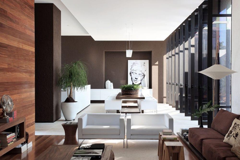 modernes wohnzimmer mit braunen wänden und wandverkleidung aus holz-essztisch braun mit modernen esszimmerstühlen weiß-weiße küche
