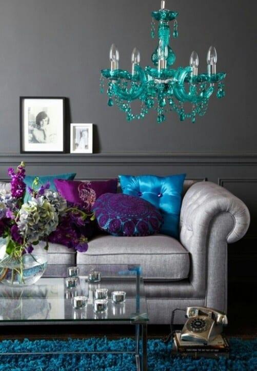 schöne wandfarben- weißes sofa mit dekokissen in blau und violett-blaue deckenlampe