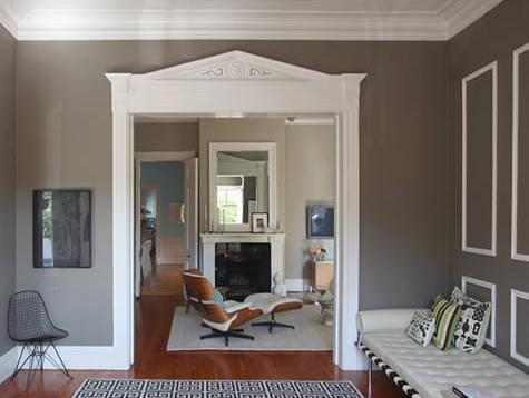 wohnzimmer mit weißem kamin und eams chair in weiß- wandfarbe taupe-lederbank weiß