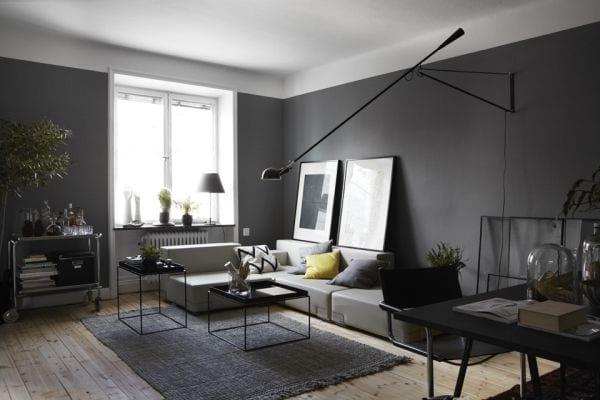 wohnzimmer wandfarbe - holzboden mit grauem teppich-weiße ledersofa mit schwarzen Metalltischen-moderne Wandleuchte