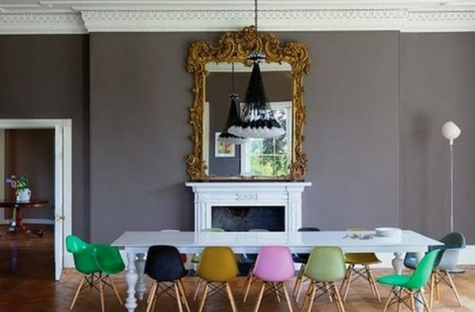 farbgestaltung wohnzimmer in grau-graue wand mit weißem kamin und Wandspiegel mit goldenem Rahmen-weiße Holztisch mit farbigen Stühlen