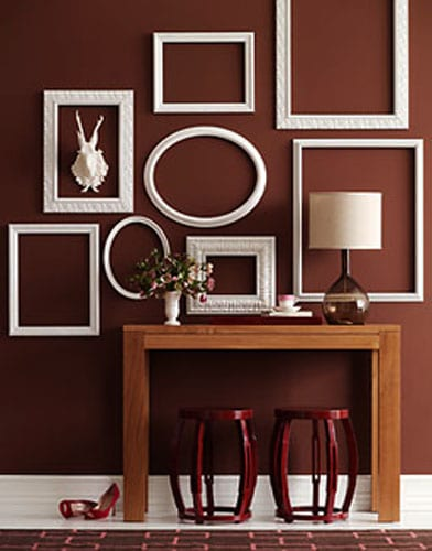 wohnzimmer braun mit brauner wand und weißen bilderrahmen- seidboard dekorieren-rote hocker