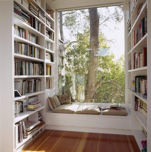 kleiner bibliothek mit weißen Bücherregalen und Panoramafenster mit weißer Fensterbank