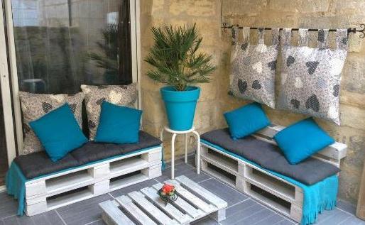 terrassengestaltung mit weißen palettenmöbeln und blauen kissen- rückenlehne aus kissen