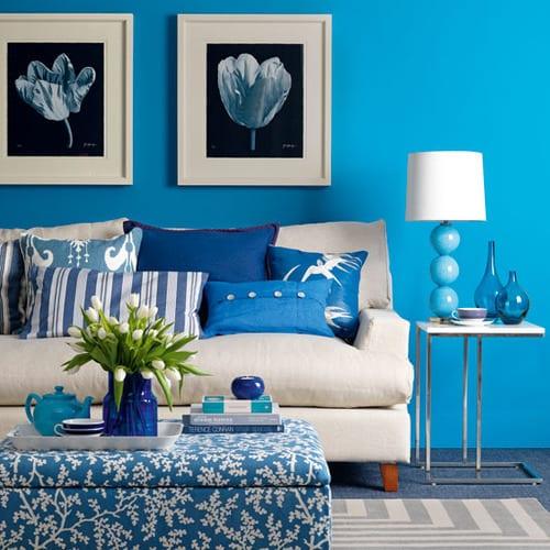 schönes wohnzimmer mit blauer wand und weißem sofa mit blauen kissen-polster hocker in blau mit weißen blumen-blaue tischlampe