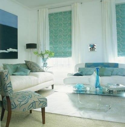wohnzimmer in blaugrün und weiß-weiße sofas mit blauen dekokissen-blaue fensterrollos