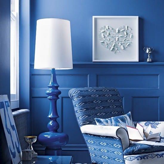 schönes wohnzimmer in blau mit blauer tischlampe und sessel in blau