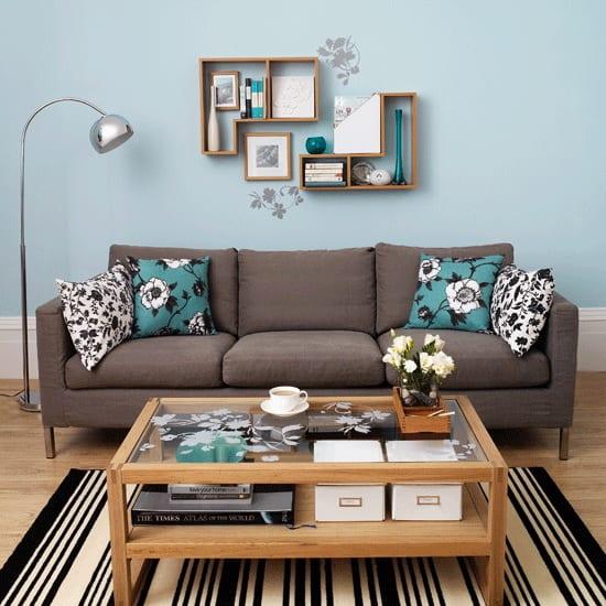 hellblaue Wandfarbe mit Wanddeko aus holzernen wandregalen und Wandtattoo blumen-sofa taupe farbe mit kissen in blumenmotiv- kaffeetisch aus holz-teppich schwarz weiß
