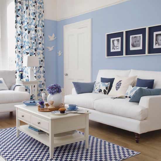 wohnzimmer einrichten mit blauen wänden und weißen möbeln-holzkaffeetisch mit schubladen-teppich mit schachmotiv in weiß und blau-gardinen weiß und blau