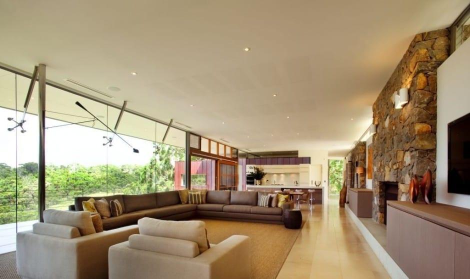 luxus wohnzimmer mit ecksofa braun und natursteinwänden-kreative glasfassade innenhalterung