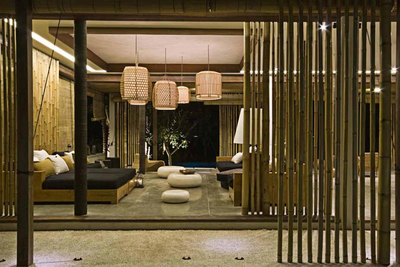 modernes Wohnzimmer mit Bambuswänden und Pendelleuchten mit Weidenkörben-Holzsofa mit schwarzen Polsterkissen und weißen runden Bodenkissen