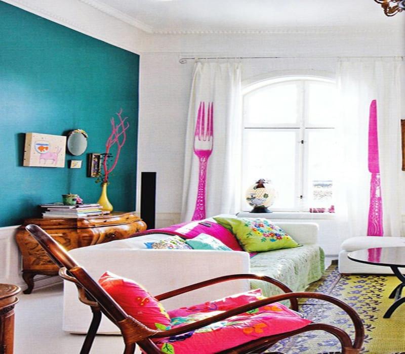wohnzimmer gestalten mit blauer Wand und gelbem teppich-Sofa weiß-Holzschaukelstuhl mit rasa Kissen-gardinen weiß mit  Messer-Gabel-Motiv in pink