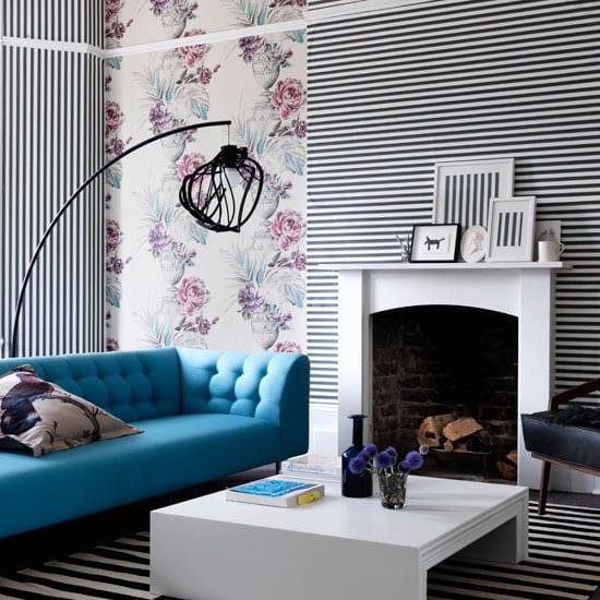 wohnzimmer in weiß und schwarz mit blauer Couch und moderne schwarze Stehleuchte-weißer Couchtisch- weiße Tapeten mit Rosenmotiv