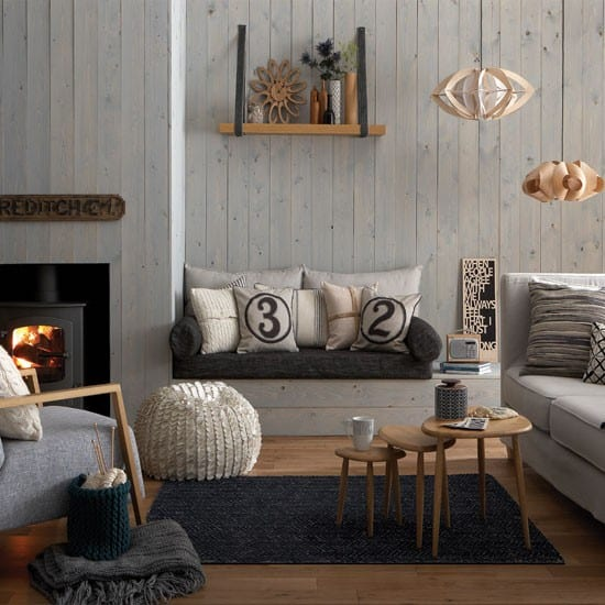 wandfarbe grau- holzsitzecke mit weißen kissen-wohnzimmer mit kamin und dekorativen holztischen-moderne pendelleuchten