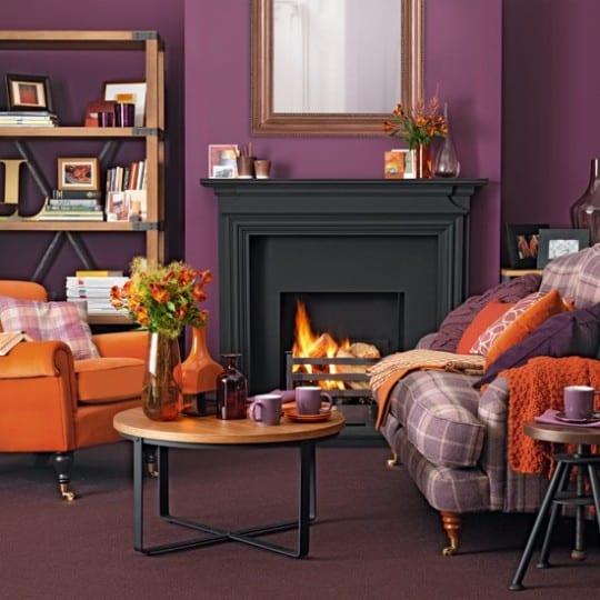 modernes wohnzimmer mit lila wänden und schwarzem kamin-polstersessel orange-textilboden violett-wandregal aus holz-kamindeko idee