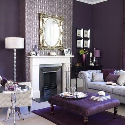modernes wohnzimmer in lila mit lila teppich und polsterhocker lila- wandtapete lila-weißer Kamin